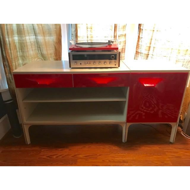 THis Raymond Loewy desk features a white body with red-orange detail. Features cabinet door that opens to a file drawer...