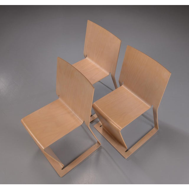 Three stacked Swedish lForm chairs in shaped and lacquered beech fins.