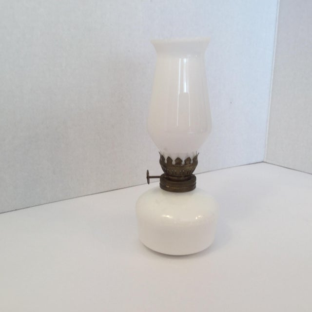 """Vintage milk glass oil lamp with brass burner and collar. The glass chimney has a scalloped top rim. The base has """"MADE IN..."""