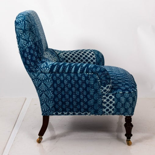 Victorian armchair upholstered in blue and white Indian fabric on wood turned legs with castors. Please note of wear...