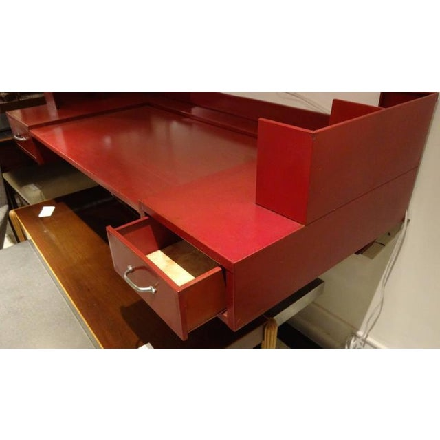 Wall-mounted desk featuring a body in red enameled metal with side top organizers and two front side drawers. The desk...