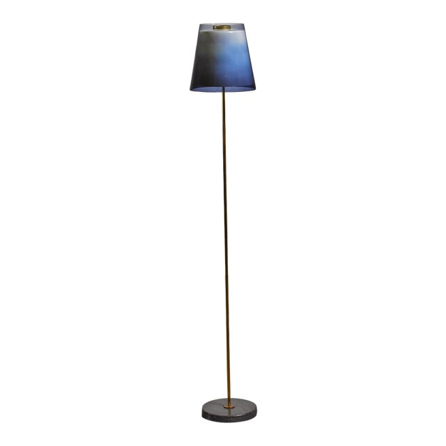 A model 30-008 floor lamp by Yki Nummi for Orno. The lamp has a brass base with a shade of two layers of plastic, one...