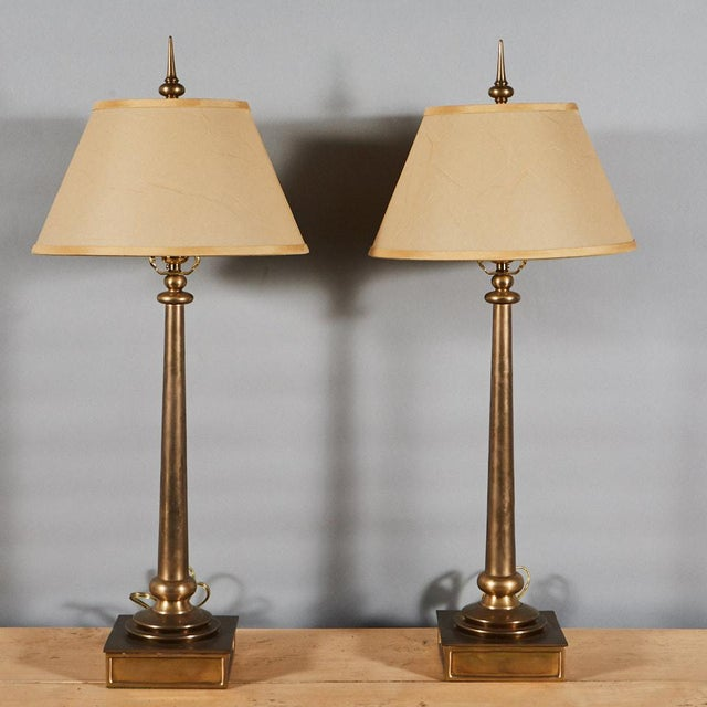 This elegant pair of Chapman brass table lamps are have plinth bases and slender columns. The pair come with custom small...