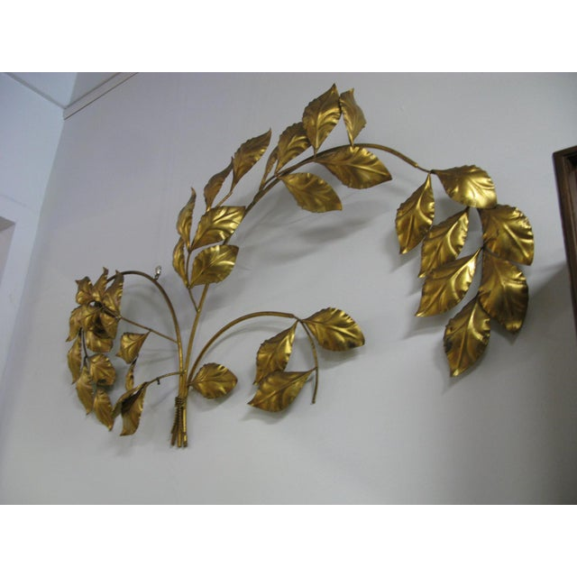 Wonderful 1960s Hollywood Regency gold leaf wall sculpture featuring a bouquet of arched branches with leaves. Measuring...