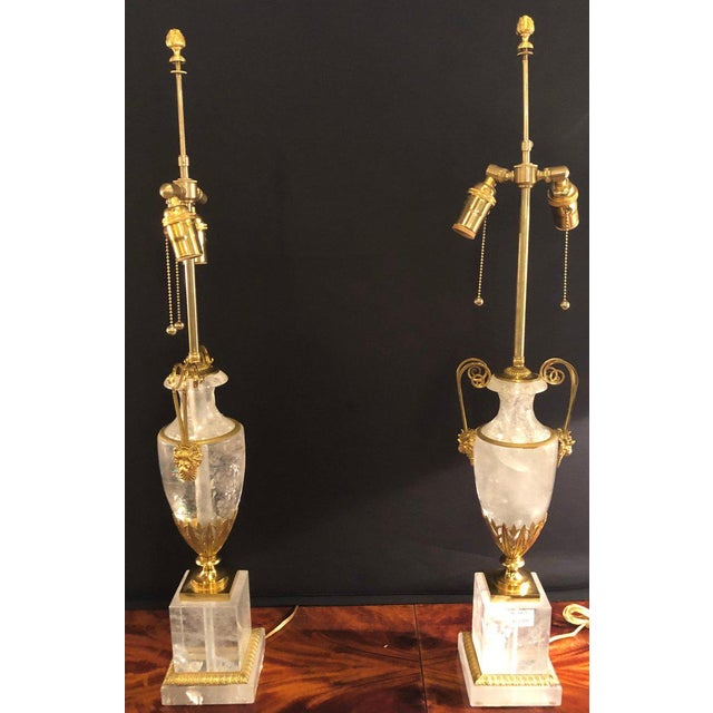 Pair of very large gilt gold and rock crystal urn form table lamps with custom shades. A pair of ormolu mounted rock...
