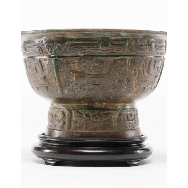 This patinated vessel on stand is a verdigris bronze round water vessel that features a Taotie (ancient Chinese mythical...