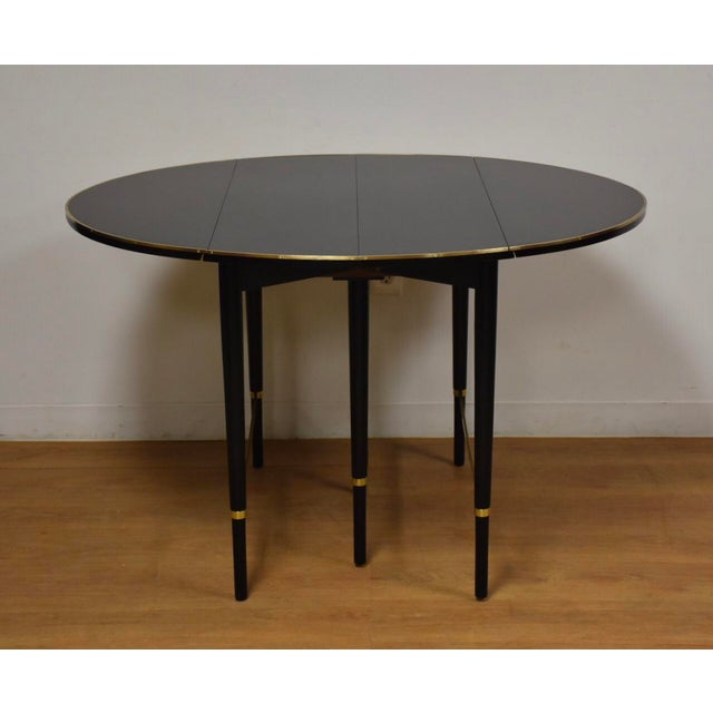 A stunning black lacquered round drop leaf dining table designed by Paul McCobb for Calvin with solid square stock brass...