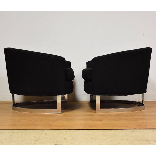 A pair of mid century modern black wool and chrome barrel back club chairs in the style of Milo Baughman. These...