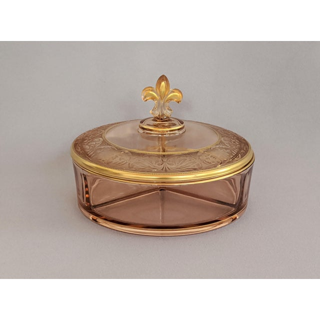 This vintage pink and gold candy dish is attributed to Fostoria. The Fleur de Lis covered dish features an intricate...