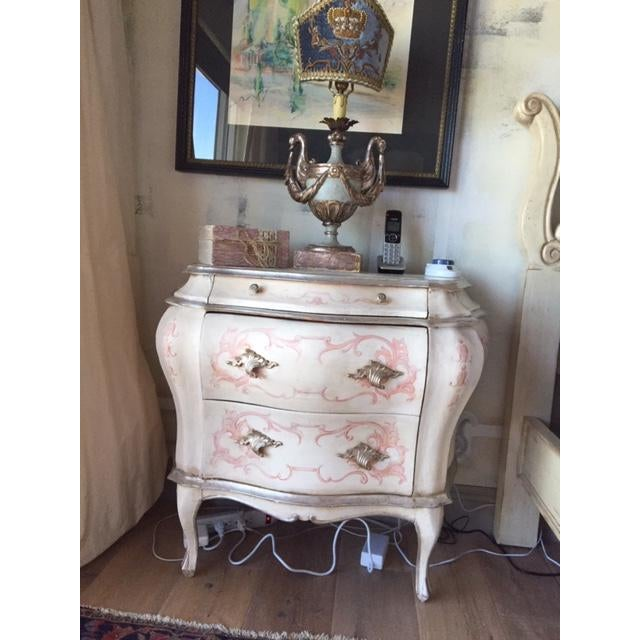 Antique Italian bombe chest. Antique white paint with soft pink hand painted details. Some silver guilt highlights.
