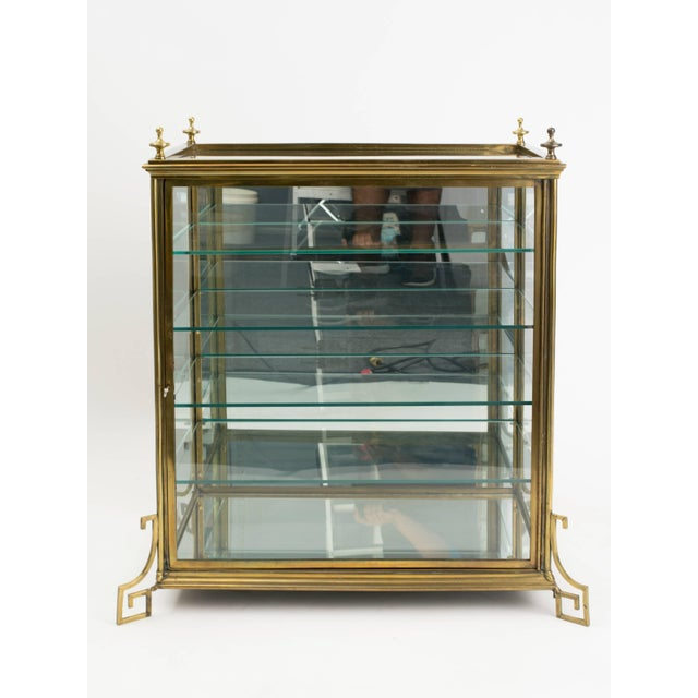 A midcentury brass curio cabinet featuring Greek key legs and mirror backing. Original lock and key.