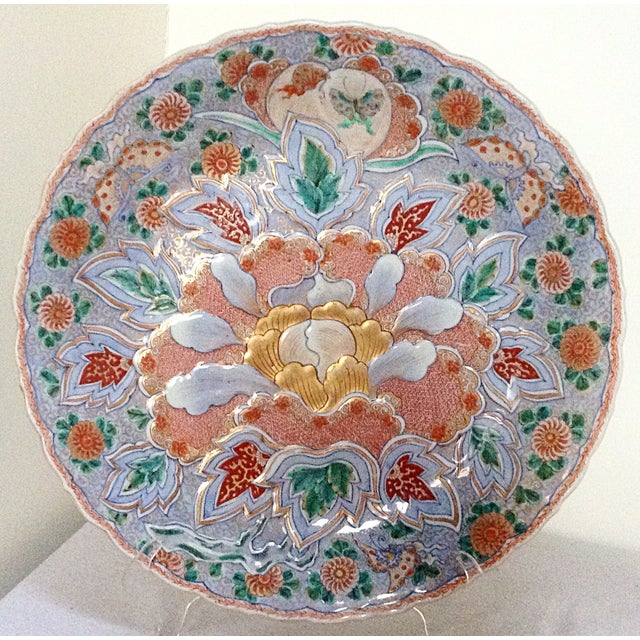 This is a large antique Asian charger that has beautiful finely detailed designs on the front and back.