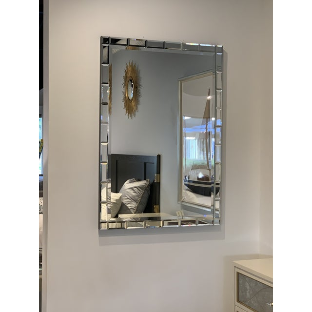 A rectangle of beveled mirror within a frame comprised of multiple rectangles of beveled mirror, this looking glass...