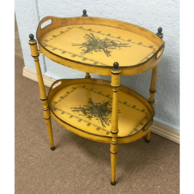 Italian tole two tier tray table on painted iron stand. In a great yellow color with a Neoclassical design. Marked made in...