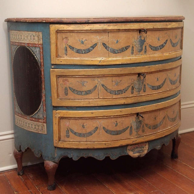 A very special piece: a rare Italian polychrome commode, in demilune shape, having three drawers over a scalloped apron...