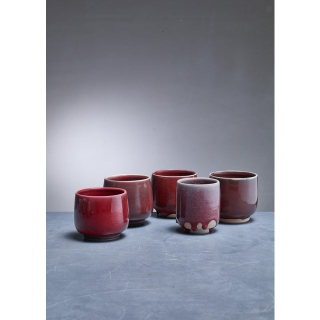 A set of five ceramic vases with a red-brown glaze finish by Rolf Palm. The pieces are signed by Palm with the year of...