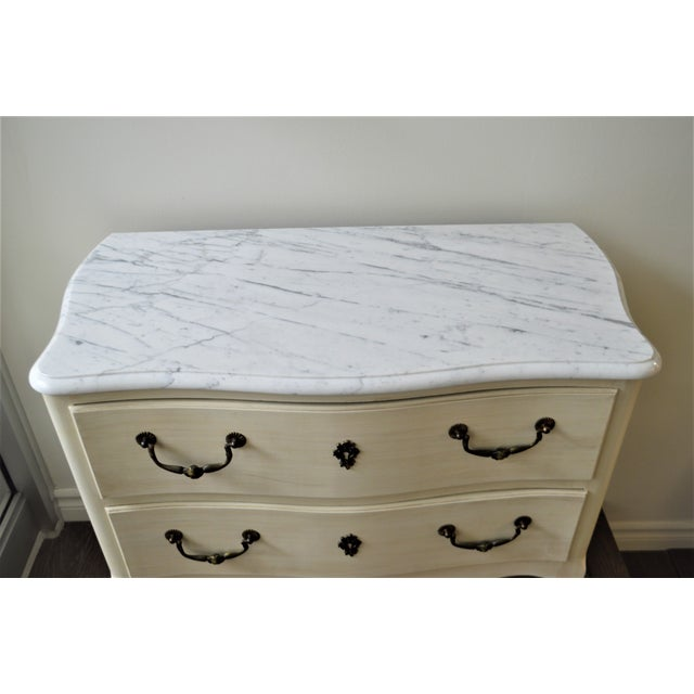 Louis XV style small commode painted in a soft white, it has the original bronze hardware and pretty bronze details at the...