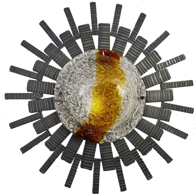 A pair of large sconces made from steel and hand-blown textured ice glass, flamed in amber and orange. The masculine...