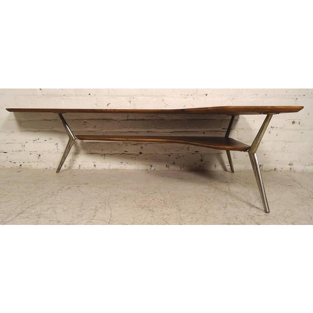 Mid-Century Modern coffee table with two tiers, kidney shape and angled legs. Great form and design from the 1960s!...