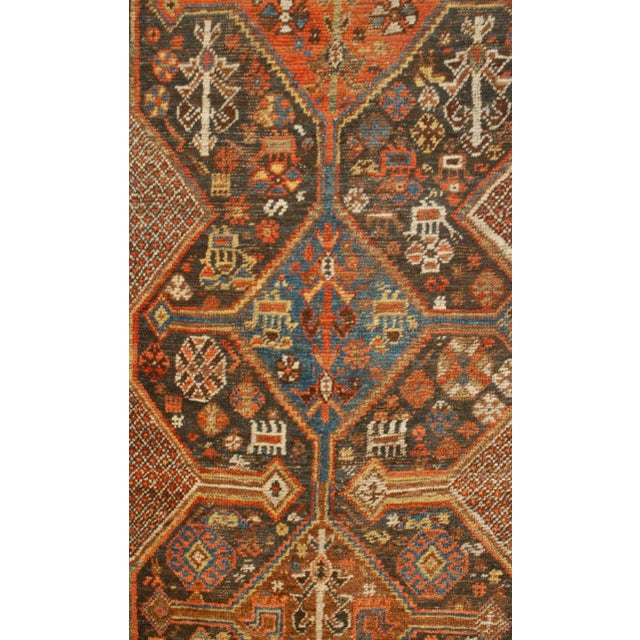 A beautiful 19th century Persian Qashqai runner with multiple central diamond medallions amidst a field of flowers,...