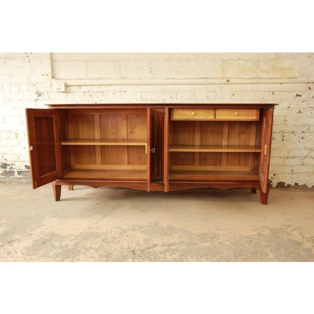Offering an exceptional 1940s French sideboard or buffet. This monumental piece features beautiful burled maple doors,...