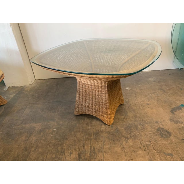 Wicker glass top dining table features unique sculptural form. Very good condition. Matching chairs also available, see...