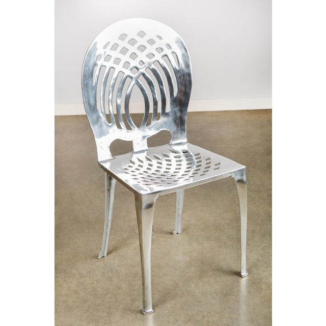 """An aluminum side chair by Statements by J. Measurements: 20"""" w x 17"""" d x 32.5"""" h, 15 pounds There are some light scratches..."""