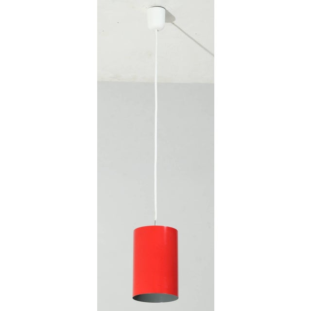 Eight minimalist, cylindrical pendant lamps by Louis Poulsen. They are made of red metal and lacquered grey inside. The...