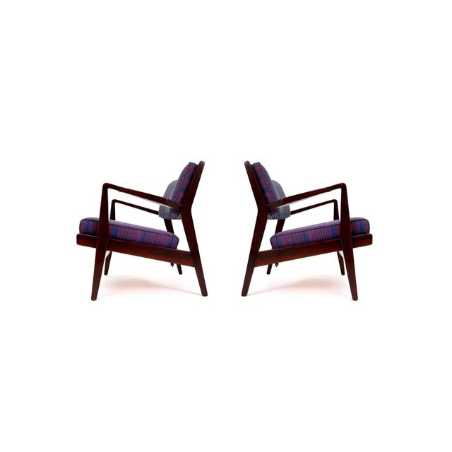 Pair of Jens Risom lounge chairs in walnut, circa 1965. Chairs have been completely refinished in a dark walnut and...
