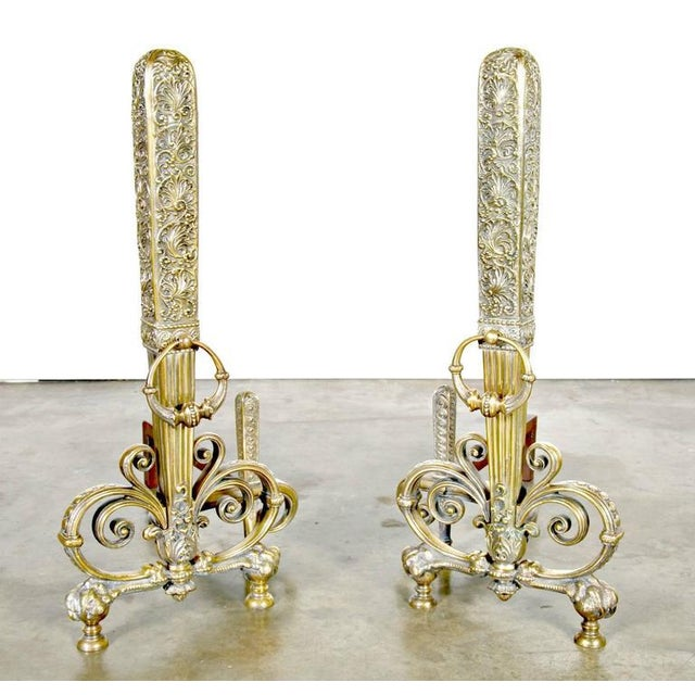 An exceptional pair of tall patinated brass and wrought iron andirons ornamented with stylized interlaced scrolls, having...