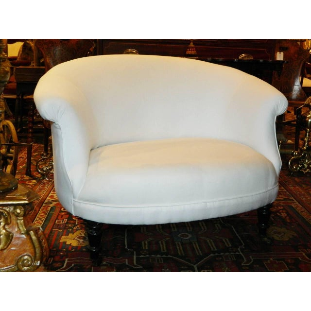 A French Napoleon III settee having continuous arched back raised on turned legs with casters, circa 1880. New muslin...