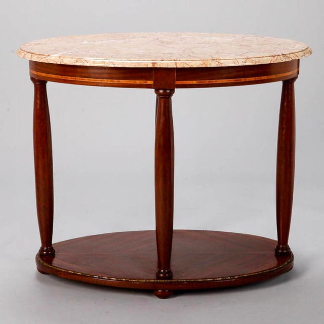Circa 1900 Directoire style center table with oval marble top in pale rouge shade supported by tapered wood columns and...