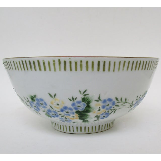 Chinese porcelain serving bowl in white glaze with hand-painted floral motif. Bowl interior has raspberry pink and pale...