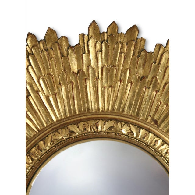 Mid-Century sunburst wall mirror with a carved giltwood frame and a convex central mirror.
