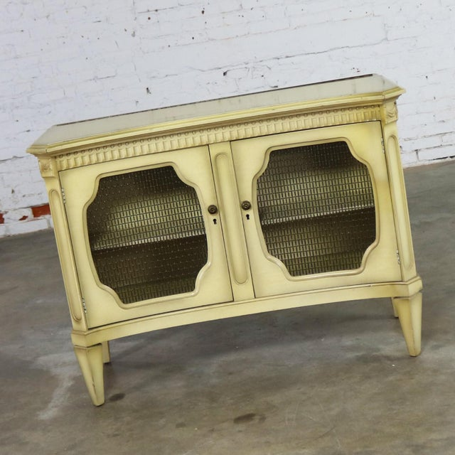 Elegant Hollywood Regency dry bar and liquor cabinet. This mid-century cabinet is done in a wonderful ivory painted finish...
