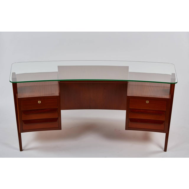 A highly striking, rare and dramatic Carlo de Carli Desk. This curvilinear executive desk is in ribbon mahogany with a...
