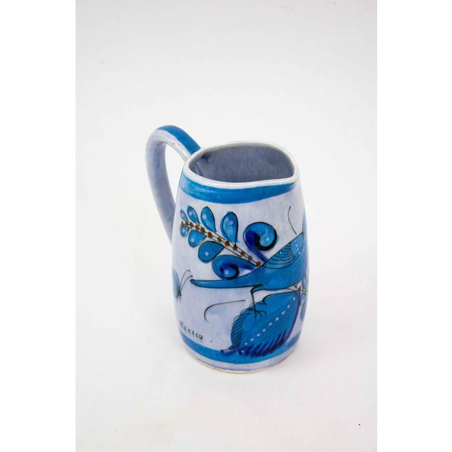 High quality mid century ceramic pitcher from Mexico. Beautiful blue glaze with charming hand painted flora and fauna. A...