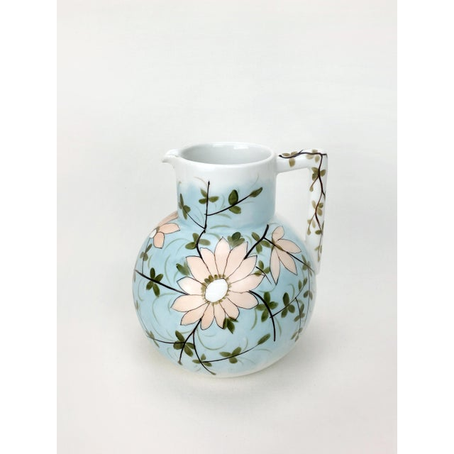 This vintage water pitcher by renowned ceramics group RS Prussia is a unique find. Features a pale pink daisy against...