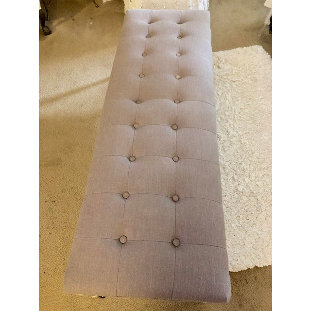Upholstered wood bench with tufted top and painted wood legs. Has rollers on the bottom. Nice long size so it can be...