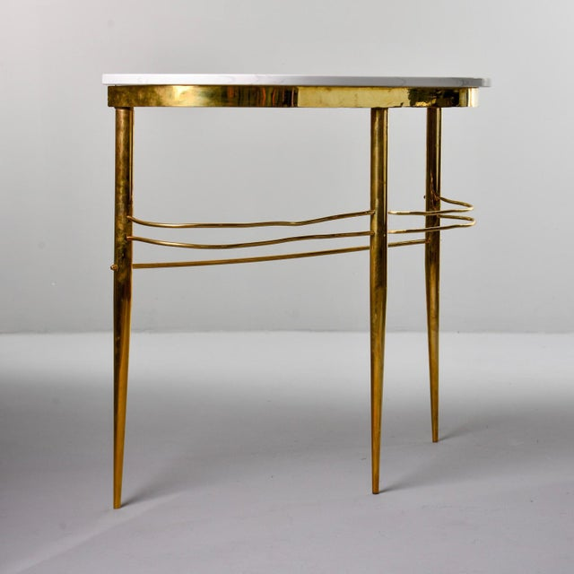 Circa 1960s console found in Italy features a stream lined brass base with three tapered legs and slender supports with a...