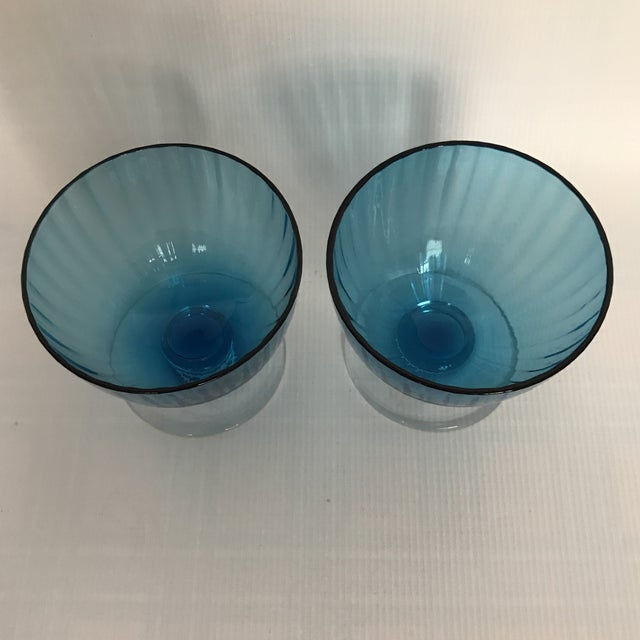 Pair of blue glass dessert cups or wine glasses with clear base.