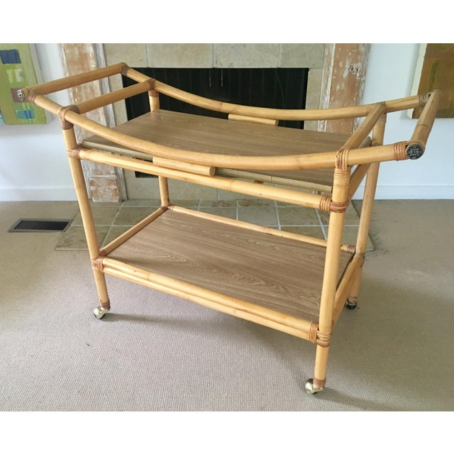 Stylish mid century bamboo bar cart with two tiers. This cart has ample storage, featuring thick bamboo handles and faux...