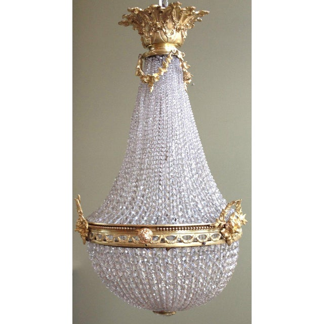 A recently rewired French chandelier from the early-20th century. Basket style with brass elements featuring laurels,...
