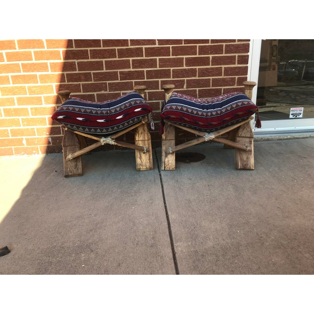 Pair of wooden camel saddle benches, rawhide tied with upholstered kilim removable seats.