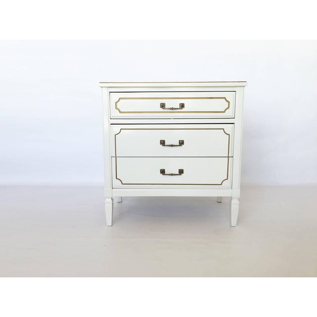 A pair of vintage mid-century French Regency paint decorated chests. Lacquered in soft white. Each night stand features a...