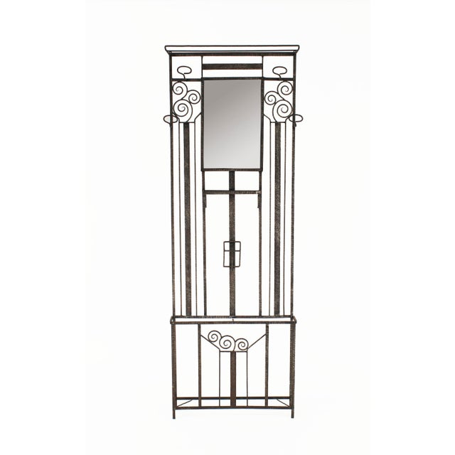 French Art Deco wrought iron standing hatrack umbrella stand with geometric and scroll designs and a rectangular mirror