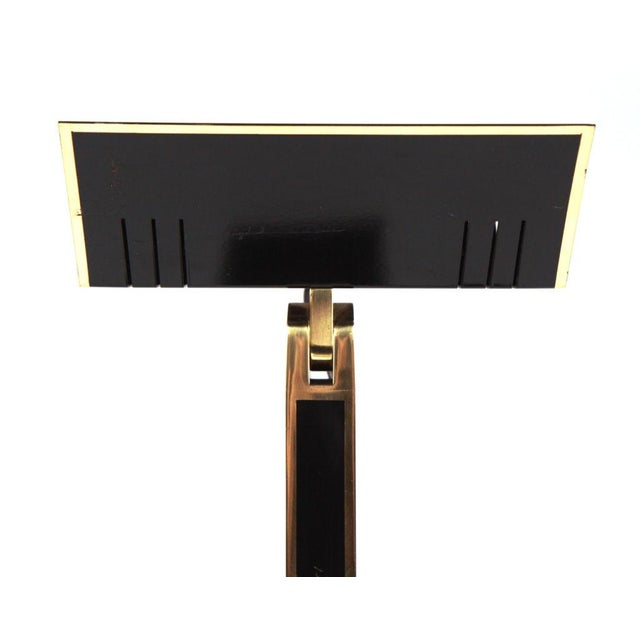 A stylish, Pierre Cardin style, very tall torchiere finished in black lacquered metal with polished brass details...