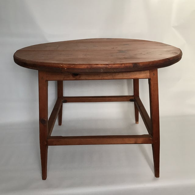 Primitive hand crafted round mid century modern style wood table with planked top and square stretcher base with tapered...