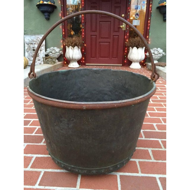 A large early 19th century riveted copper apple butter cauldron with forged iron handle. Lovely aged blue-green patina....
