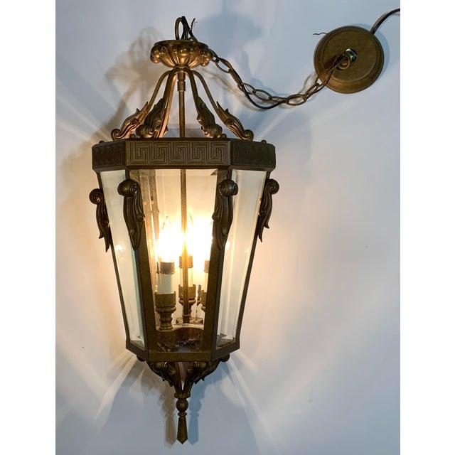 Vintage hanging lantern Made Of metal with three 60/watt light. Beveled glass on six sides, beautiful Greek key top...